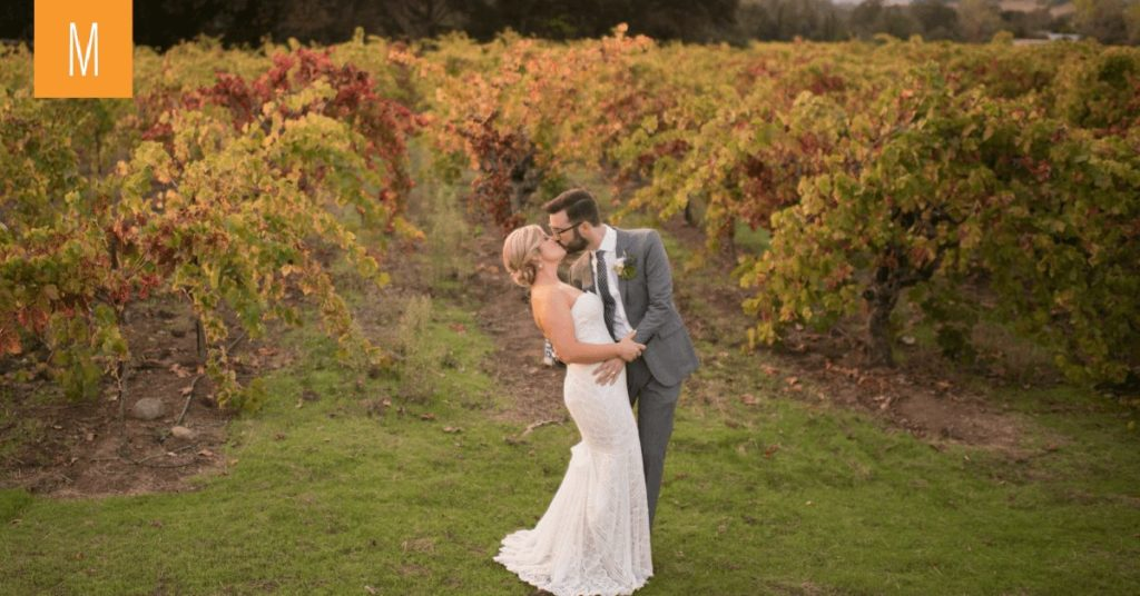 Romantic photo of a bride and groom kissing in front of fall turned grape vines.