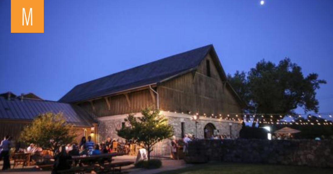 Rustic stone & wood barn with market string lights and moonlight glowing with guests mingling. Finding a wedding venue is easy with Milestone.