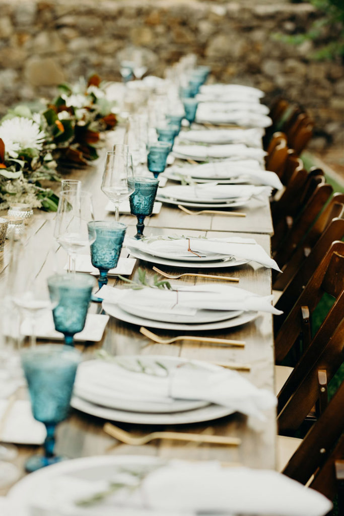 Table setting for a winery wedding with blue goblets