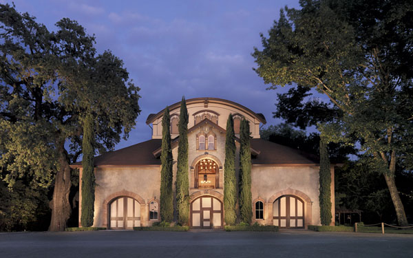 twilight over the carriage house exterior at Charles Krug Winery. Surrounded by heritage oak trees and juniper